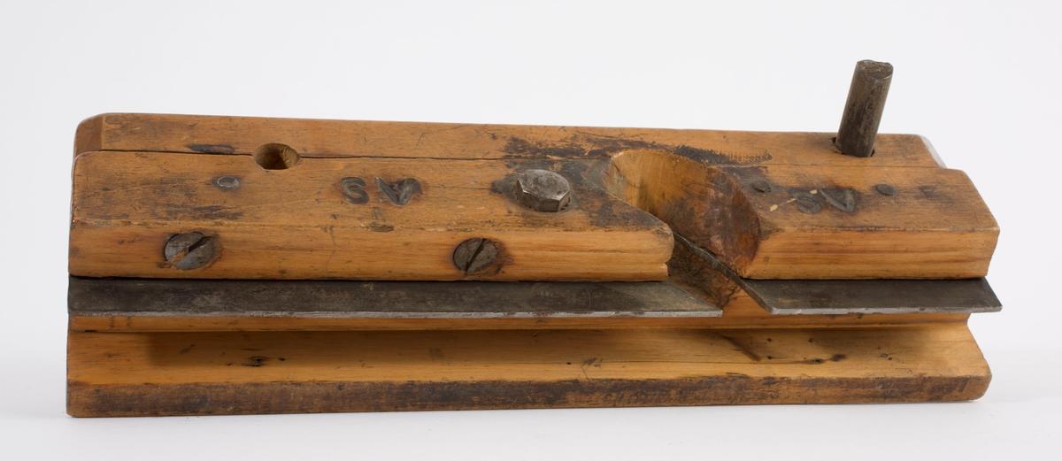 """Nothøvel i tre uten kile og høveljern. På høyre langside er """"SV"""" brent inn to ganger. Styrekant på venstre langside. Gjennomgående jern-/stålpinne i fronten på høvelstokken."""