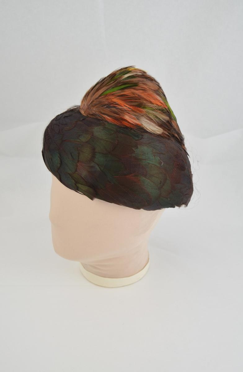Filthatt heldekorert med fjær. Grønne horisontalt lagte fjær på hattens nedre del, pull med fargerike fjær. Netting på utsiden. Form: liten, bremløs.