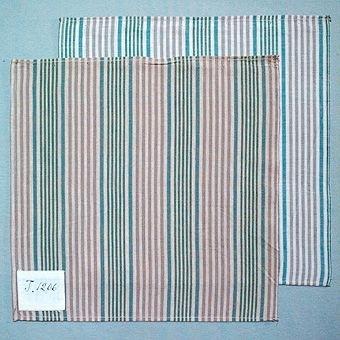 """Två randiga vävprover i bomull, vävda i tuskaft. Varp i naturvitt, grönblått, blått och grått, inslag i beige (96:1) resp. naturvitt (96:2). Märkta med påsydda tyglappar med texten: """"T. 1206"""" (96:1) resp. """"T.1205"""" (96:2). Vävproven sitter ihopfästade med snören, med ytterligare tjugosju vävprover ( inv.nr 77 - 95, 97 - 100)."""