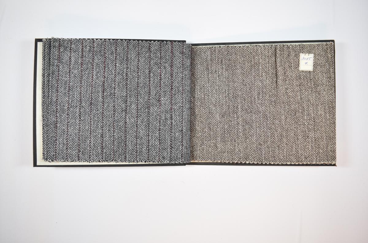 Rektangulær prøvebok med seks stoffprøver og harde permer. Permene er laget av hard kartong og er trukket med sort tynn tekstil. Boken inneholder middels tykke to- til trefargede stoff med fiskebenmønster og striper. Kyperbinding/diagonalvev. Alle stoffene ligger brettet dobbelt i boken slik at vranga dekkes. Stoffene er merket med en firkantet papirlapp, festet til stoffet med metallstifter, hvor nummer er påført for hånd.   Stoff nr.: 3015/1, 3015/2, 3015/3, 3015/4, 3015/5, 3015/6.