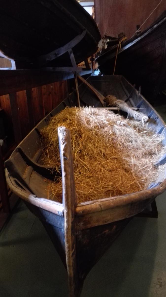 """Velbrukt tjørebredd føringsbåt med raud botnsmurning. Spegel bak, med defekt feste for ror. To tofter og eitt par keipar ved den bakre tofta. Manglar tiljer. To """"kodlarar""""  (til fortøying og til å binda ting fast) bak og to framme (den eine er defekt).  Båten ser ikkje ut til å ha hatt segl."""
