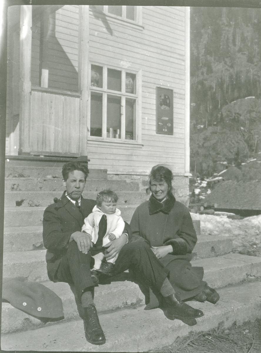 Kvinne, mann og barn sitter på ei trapp, muligens trappa til Foss-bygningen, Sør-Aurdal.