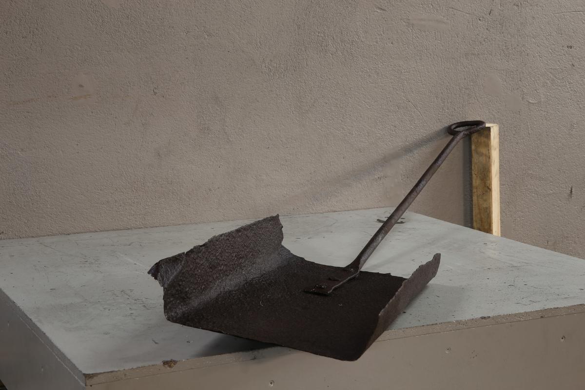 Redskap: Jernbrett med skaft. Skaftet er klinket fast i jernbrettet.