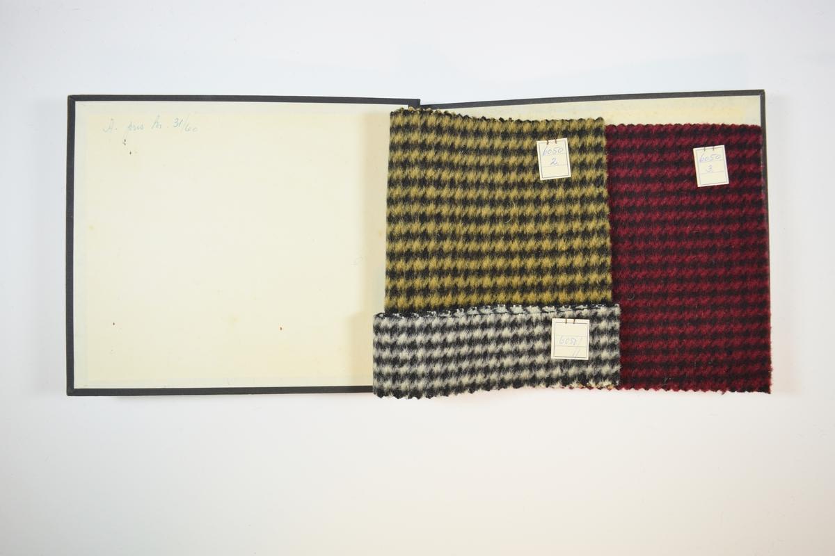 Rektangulær prøvebok med harde permer og tre stoffprøver. Permene er laget av hard kartong og er trukket med sort tynn tekstil. Boken inneholder tykke ullstoff med stripe- eller rutemønster. Stoffene ligger brettet dobbelt i boken slik at vranga skjules. Vevmønsteret er mer synlig på vranga. Stoffene er merket med en firkantet papirlapp, festet til stoffet med metallstifter, hvor nummer er påført for hånd.   Stoff nr. 6050/1, 6050/2, 6050/3.