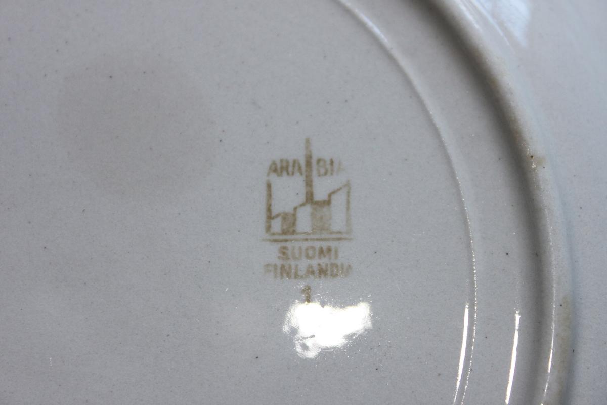 Flat tallrik av flintgods. Vit glasyr. 30 mm brett, slätt bräm. Under botten stämplad med brunt ARABIA SUOMI FINLAND kring bild av fabrik.