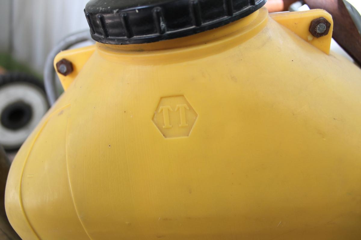 Behållare och spruta för bekämpningsmedel. Avsedd att bäras på ryggen.  Behållaren är tillverkad i gul plast med svart plastlock. Behållaren sitter i en metallställning som har två bruna läderremmar fäst upptill. Remmarnas andra ände är avsedd att fästas i metallringar i ställningens nederdel. Från nederdelen finns det också ett långt handtag försedd med svart gummi i yttre änden. På behållrens ena sida finns en röd metallplatta till vilken det löper ett koppar- och plaströr från behållaren. Från plattan löper det en svart- och turkosrandnig plastslang, vilken avslutas i ett kopparrör med munstycke. Sprutan regleras med ett handtag.