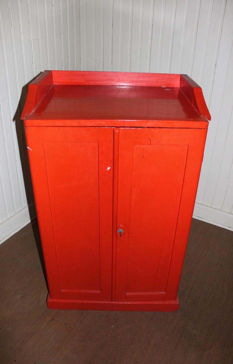Kommod/skåp i rödmålat trä med två luckor. Gångjärn och lås med nyckel i metall. Två hyllplan på insidan med hyllremsor på kanterna.