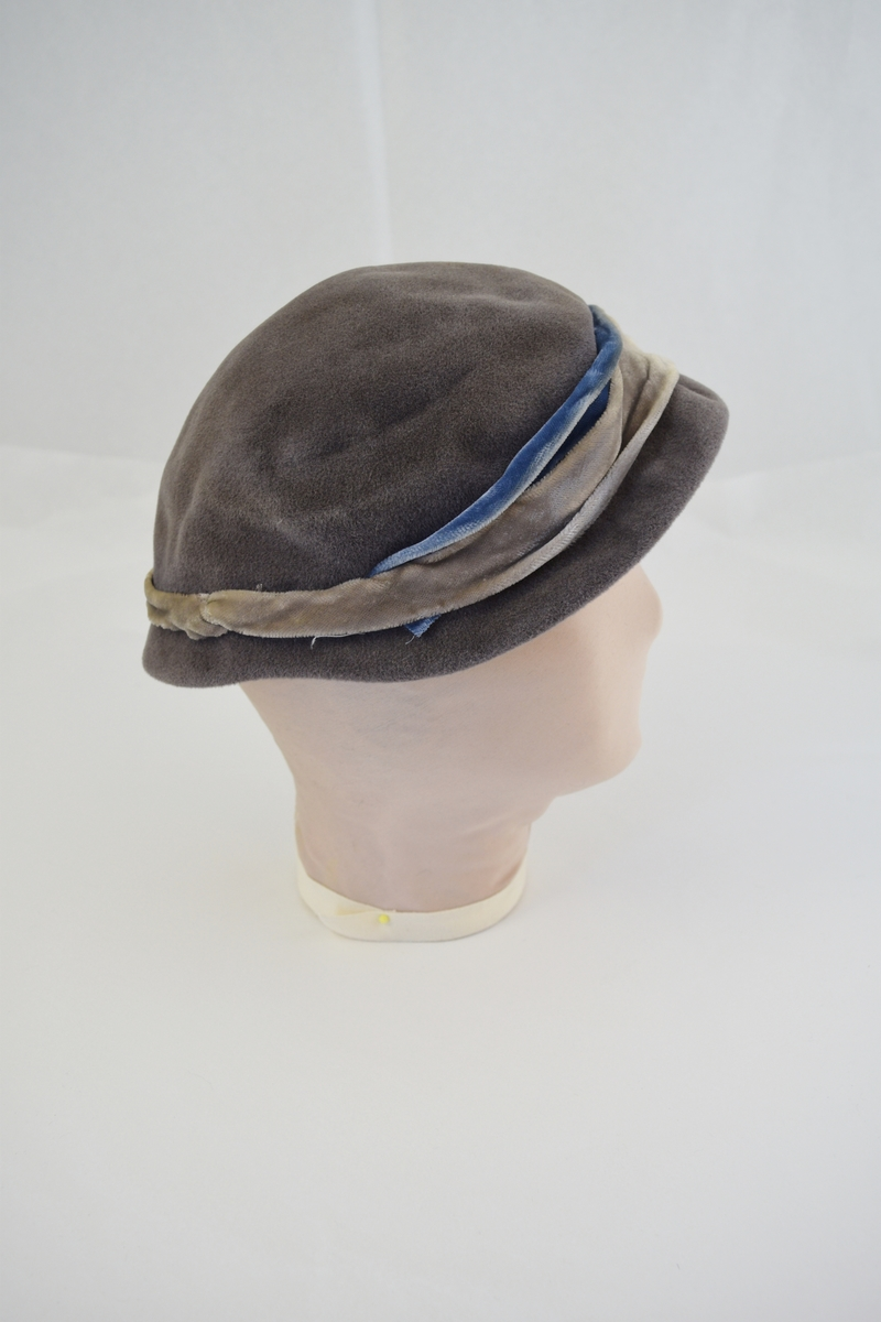 Hatt i fløyellstoff, rundform. Dekorert med påsydde bånd av fløyel. Form: bolleform