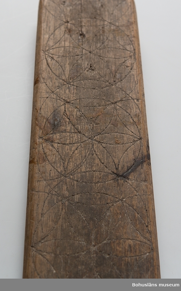 """Platt, rektangulärt redskap med handtag i form av en häst. Ovansidan har ristade rosetter som går in i varandra. Framtill är brädan kluven som övre delen på ett hjärta. På en sida om handtaget är årtalet """"1822"""" inskuret och på motsatta sidan är initialerna """"IODL"""" inskurna. Handtaget är inskjutet i ett spår och fästat med två grova spikar. Hästen är lagad med en ny träbit vid främre benet. Är troligtvis en friargåva. Kavelrullen att linda tyget runt saknas. Har mörknat på grund av användning. Skadedjursangrepp.  Litteratur: Nylén, Anna-Maja, Hemslöjd, Håkan Ohlssons förlag, Lund, 1978, s. 359-363. Fredlund, Jane, Stora boken om livet förr, ICA-förlaget, Västerås, 1981, s. 40-49, 170-177. Sörensen, Steinar, Mangletreet-Glatteredskap og festegave, Glomdalsmuseets småskrifter nr. 3, Engers Boktryckeri A/S, Otta.  Ur handskrivna katalogen 1957-1958: Kavelbräde. dat. 1822 Mangelbräde. L. 70,5 Br.11 Trä med inskurna mönster. Handtaget löst, enstaka maskhål. Lagad 15/11-1990  Lappkatalog: 72"""