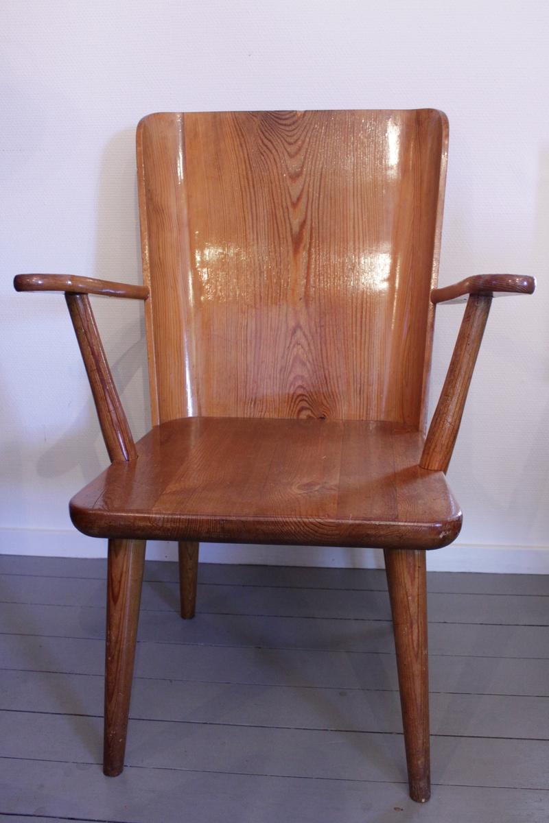 Karmstol med svängd rygg i fanerat trä. Hel ryggbicka och ben är fastskruvade med skruvar och tydliga stora skruvhuvuden. Rund men avsmalnande nedtill.