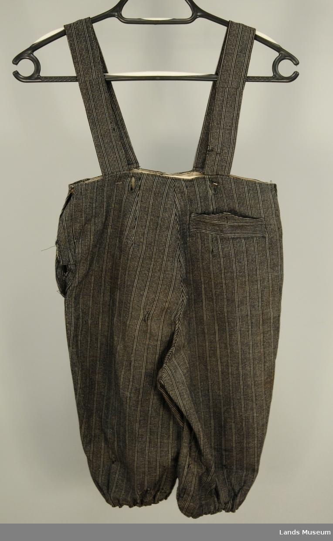 Guttebukse i stripete ullstoff, rynket ved knærne med strikk. Seler av stoff. To knapphull i linningen. Trykknapp i sidene. Belagt oventil med kvitt bomullstoff. En lomme bak.