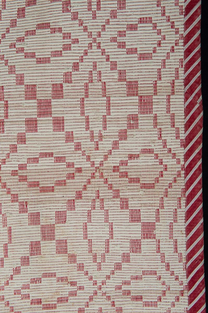 Den röda och vita varpen bildar rutor till ett optiskt mönster. Överkastet är hopsytt på längden av två våder och kantat med snedremsor i rött- och vitrandigt bomullssatin.