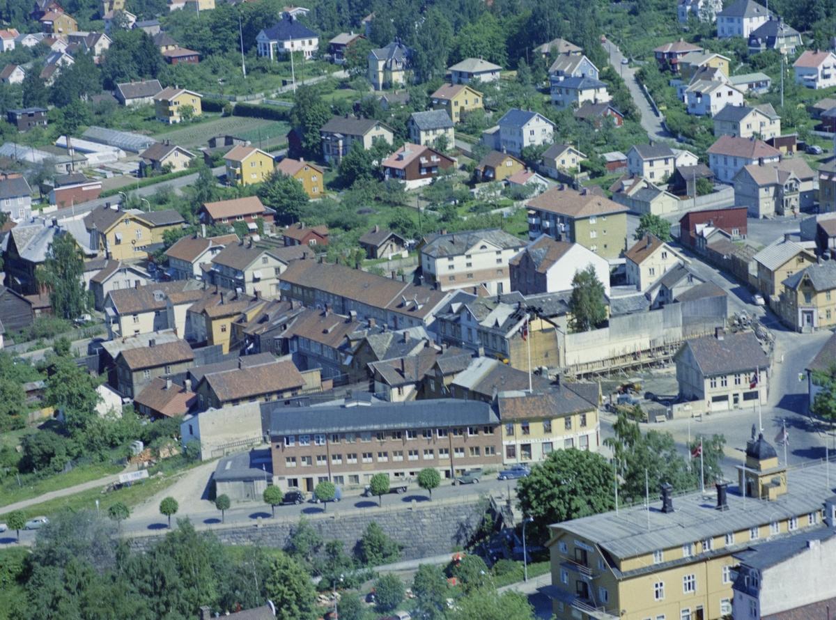 Flyfoto, Lillehammer, bebyggelse, Nærmest i høyre hjørne Victoria Hotell. Brubakken på andre siden av Mesnaelva med den gang Lillehammer Samvirkelag. Lilletorget til høyre med Stensrud skoforretning. Gamlevegen går opp mot høyre og i bakgrunnen til venstre ligger Christensens gartneri
