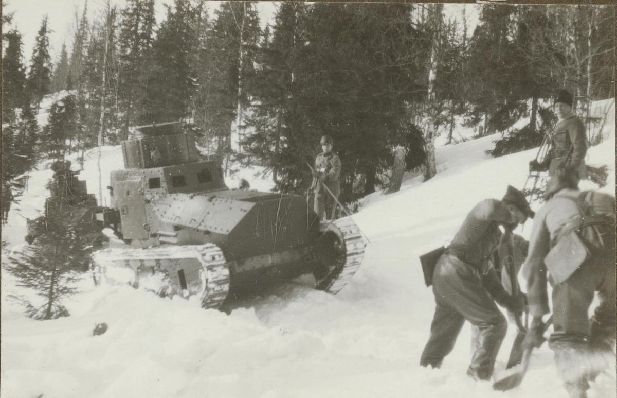 Två stridsvagnar m/1921 (eller m/1921-1929) på väg uppför backen. Soldater rensar körvägen från snö med spadar. Stridsvagnskursen vid Göta livgardes stridsvagnsbataljon övar i fjällmiljö.