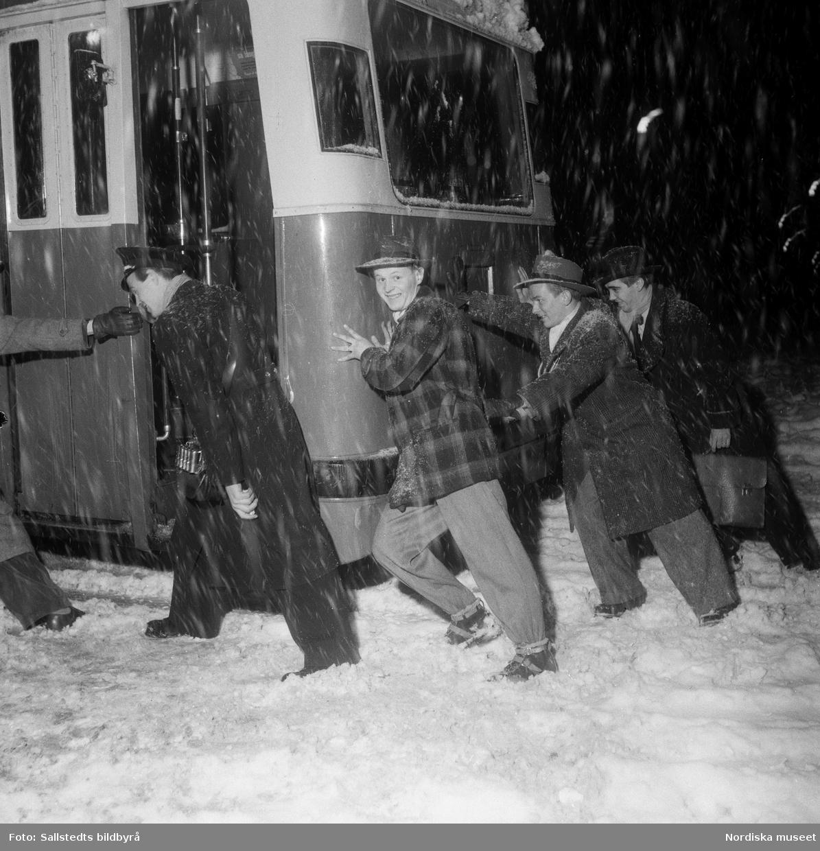 """""""Snöfall i Stockholm"""". Fem män skjuter på buss som fastnat i djup snö, Stockholm."""