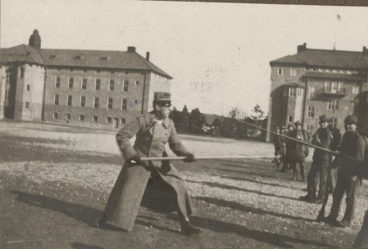 En soldat fäktar med spade. Soldater i rad står och iakttar händelsen.