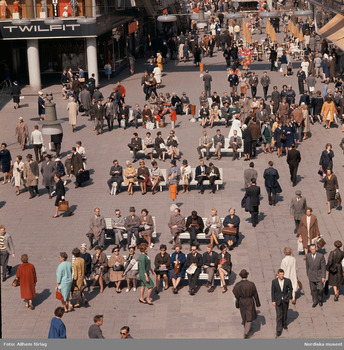 Sergelgatan, Stockholm. Människor som sitter på bänkar.
