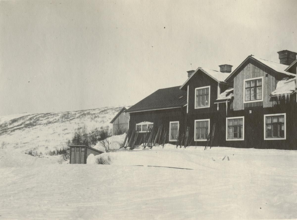 Ett trähus i fjällen med skidorna ställda mot husets framsida. Framför huset finns en mindre byggnad. Bakom huset syns en kortsida till ytterliga ett trähus.