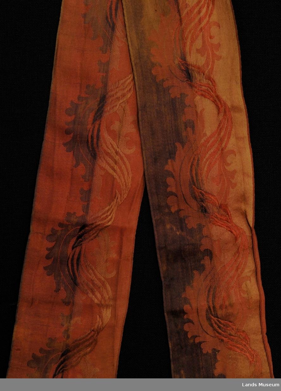 Silkebånd med bølgete mønster i midten langs hele. Falmet.