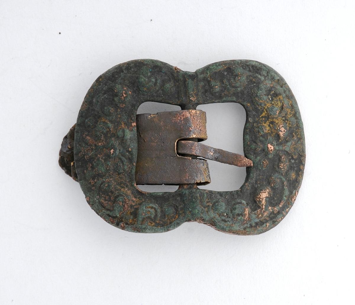 Knebandspenne støypt i messing (bronse). Rektangulær form, men svinga inn på midten. Stolpe, kalv og tann smidd i messing.(?). Irra.