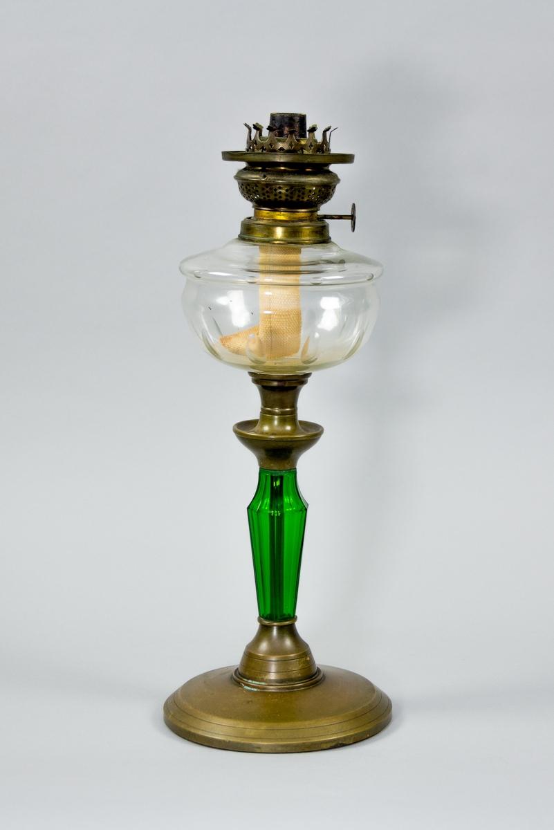 Fotogenlampa av glas och mässingsplåt. Lampfot med brännare i mässing. Oljehus i klart glas med slipad dekor. Dekorativ mittdel i mässing. Nedre delen i form av grönt glas med fasade kanter, avsmalnande nedåt. Foten är av mässingsplåt, rund och svagt välvd.