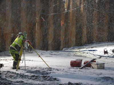 Arkeolog sikter inn totalstasjonen i snøvær. (Foto/Photo)