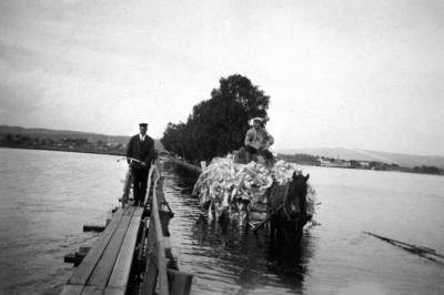 Svart-hvitt foto fra 1927. Gangbru med mann og hestetransport med stort lass som kjører på ordinær bru i flomvann.. Foto/Photo