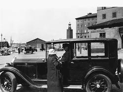 En kvinna talar med en chaufför som sitter i en parkerad Bui