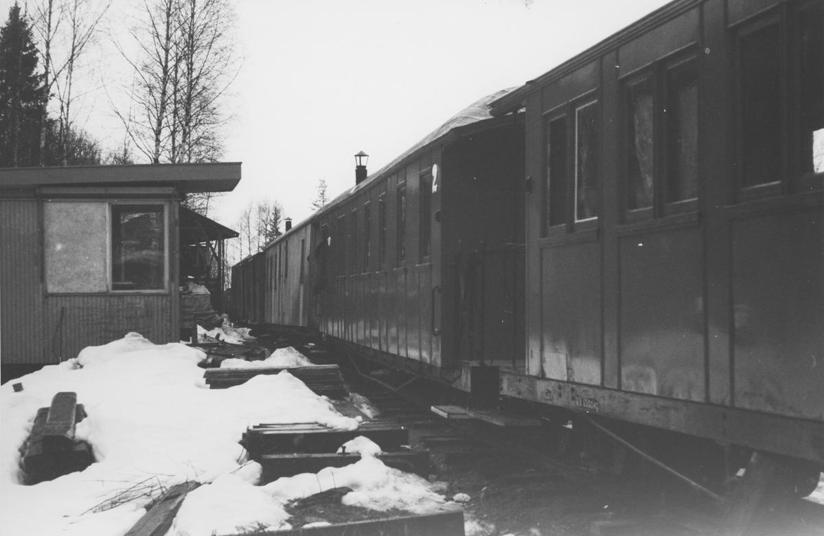 Museumsbanen Urskog-Hølandsbanens personvogner vinterlagret utendørs på Bingsfoss stasjon.