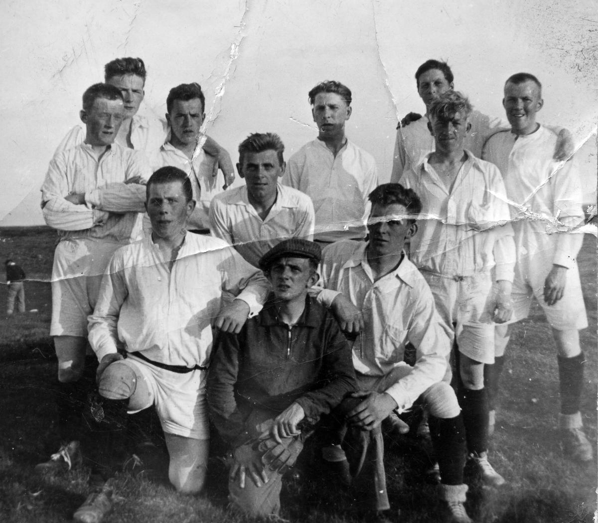 Fotball-laget AIL (Aust-Finnmark Idrettslag). En av spillerne til venstre i bildet er Mathis Henriksen, opprinnelig fra Nesseby. I bakgrunnen ses litt av luftskipsmasta på Vadsø-øya. Bildet er antakelig tatt på fotballbanen på øya, ca. 1935.
