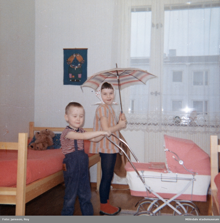 3-årige Lars-Åke hållandes en dockvagn och 7-åriga Ilse i sitt alldeles egna nya rum. Familjen har precis flyttat till en ny modern lägenhet i Tynnered efter att ha bott omodernt och trångt i Krokslätt. Året är 1967.