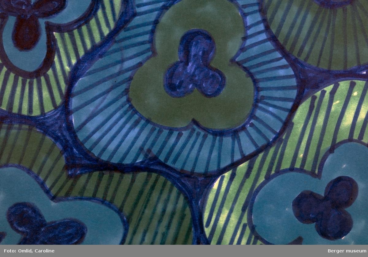 Mønster av blomster med tre kronblad innrammet av brede felt rundt, de yttertste skrarvert