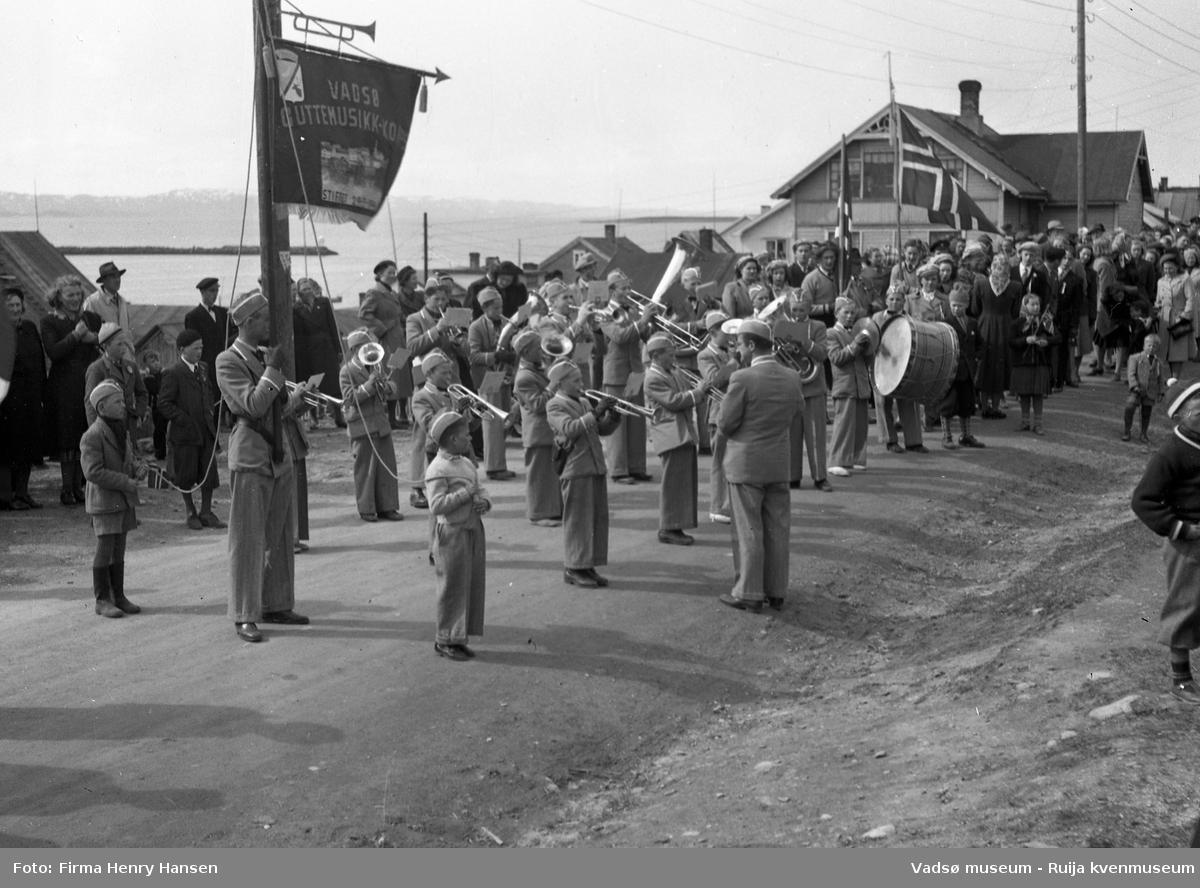 """Vadsø 17 mai 1951. 17-mai toget har stoppet i Nyborgveien, foran """"Alders Hvile"""". Vadsø Guttemusikkorps spiller og vi ser en fanebærer med fane. Bakerst i venstre billedkant ser vi havnen og deler av moloen. Publikum, både barn og voksne sees langs 17. maitoget."""