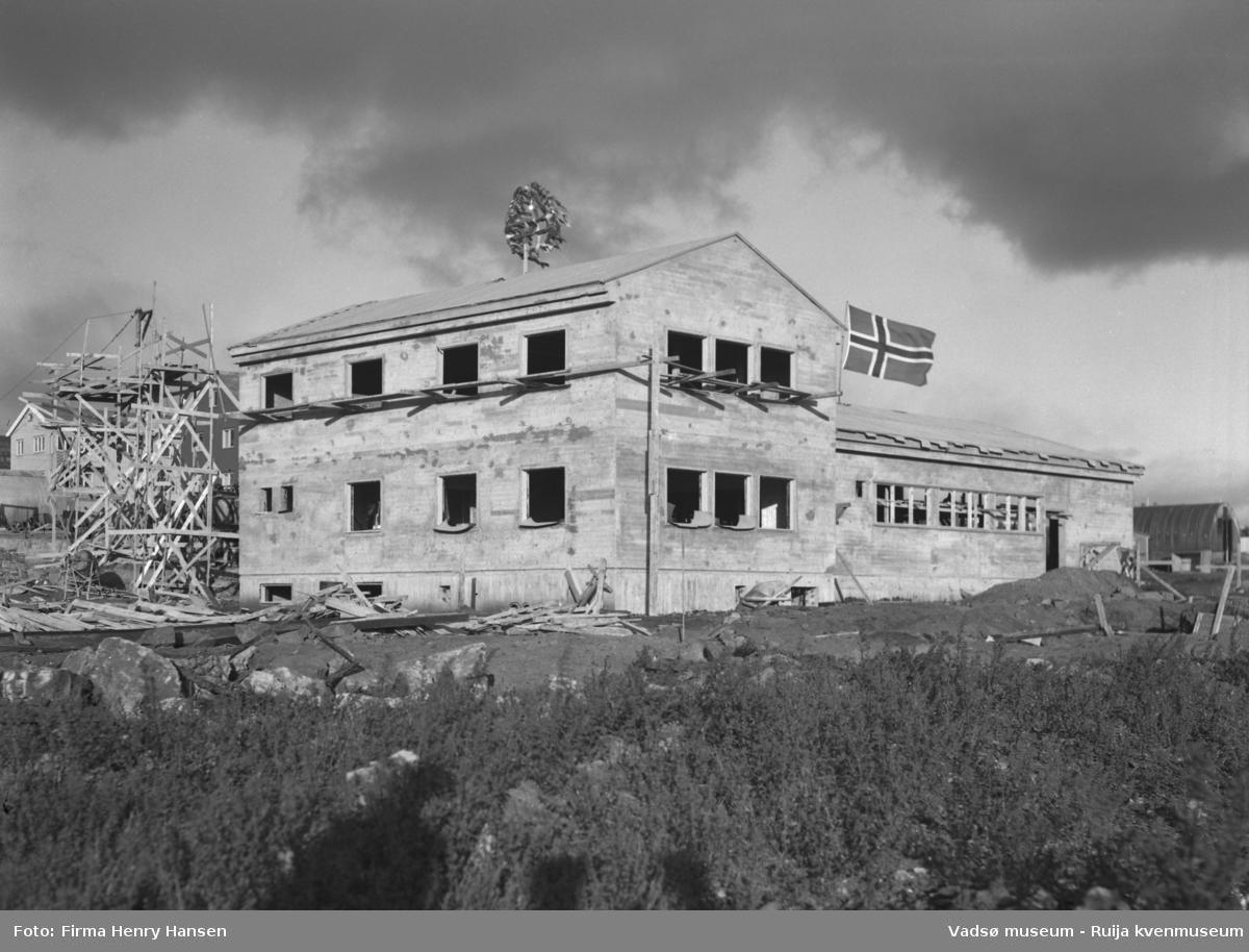 """Vårbrudd 1949.  Bildet viser Vårbrudd under oppføring. Bygningen har nå """"tett tak"""" og vi ser kransen som er heist på mønet og flagget vaier. Forskalinger og bygningsmaterialer ses rundt bygningen. I høyre billedkant skimtes en nissenbrakke."""