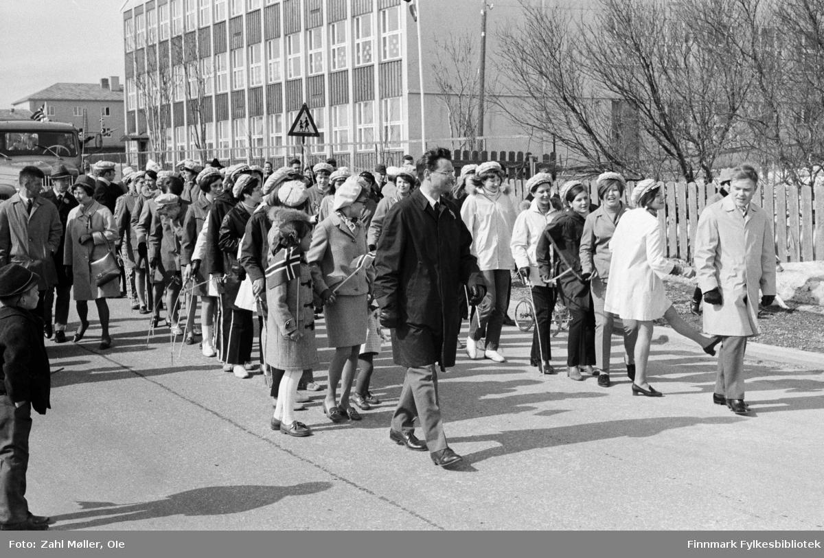 Vadsø 17.5.1969. Et imponerende stort 17.mai tog passerer kirken. 6 faggbærere med norske flagg og to finske flagg kan sees foran i toget. Fotoserie av Vadsø-fotografen Ole Zahl-Mölö.
