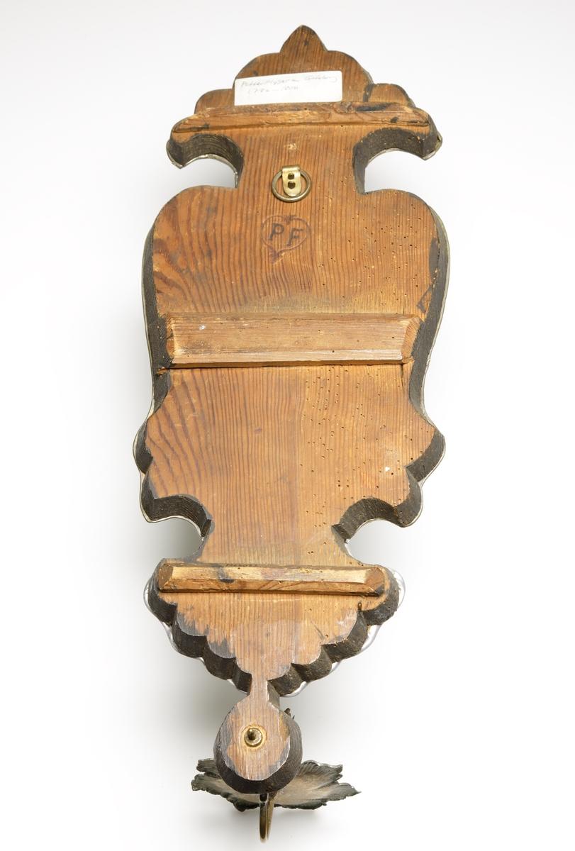 Lampett i spegelglas, med mässingsljushållare. Graverat, formskuret spegelglas. Spegelglaset fasthållet med blylist.  Bakstycke av trä, utsågat ur en och samma bit. Den är monterad med två vertikala förstärkningar.