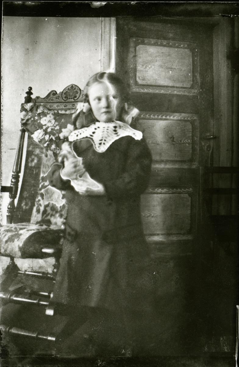 Jente ved gyngestol, ca 1910-1915.