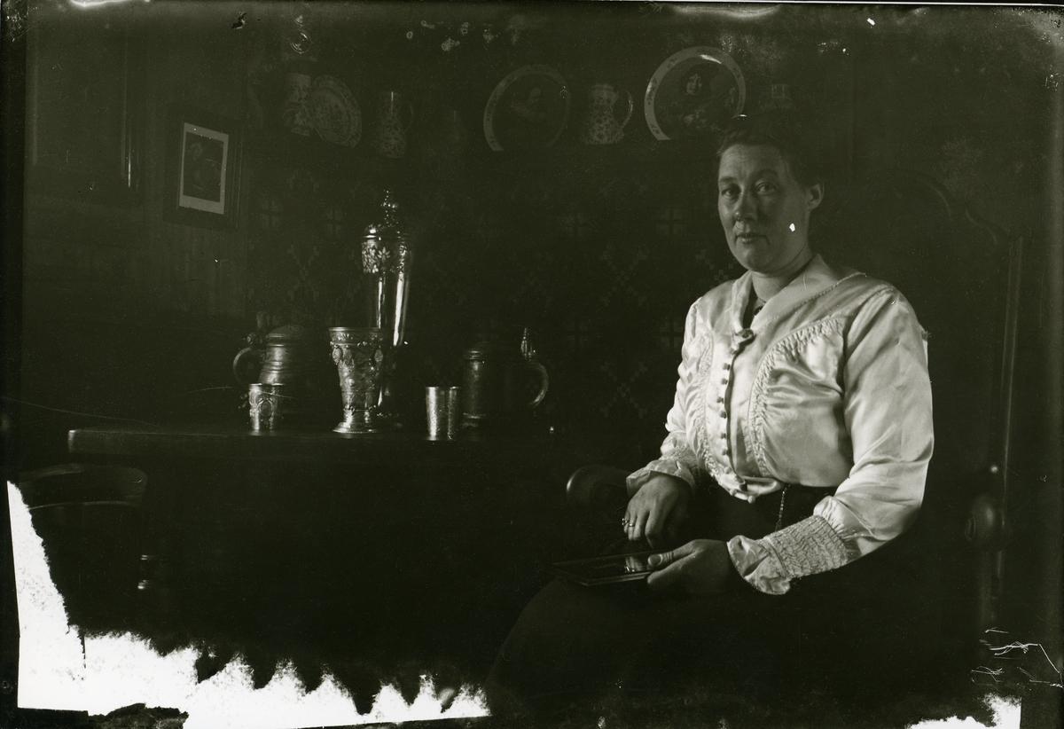 Ei kvinne sit på ein skinnstol ved eit bord. På bordet står mugger i sølv samt ein pokal.