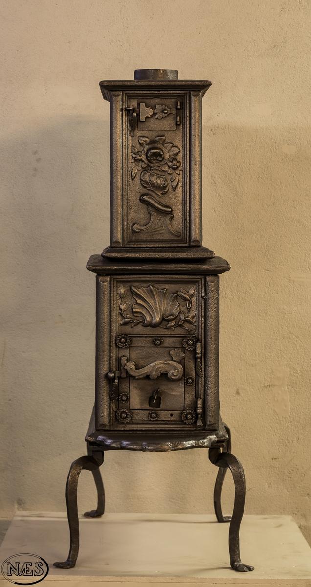 Ovn i to etasjer på smidd krakk med ovnsluke på kortside og røykuttak i topplaten. På langsiden i 1.etg vulkan som våpensmed med essen til høyre og rokokko ornament til venstre. På kortside 1.etg musling øverst og innskrift i nedre halvdel. Langside 2.etg har en uregelmessig åpning med fyldig og symmestrisk blomsterrokokko. En blomstervase på rokokko ornament preger kortside 2.etg.