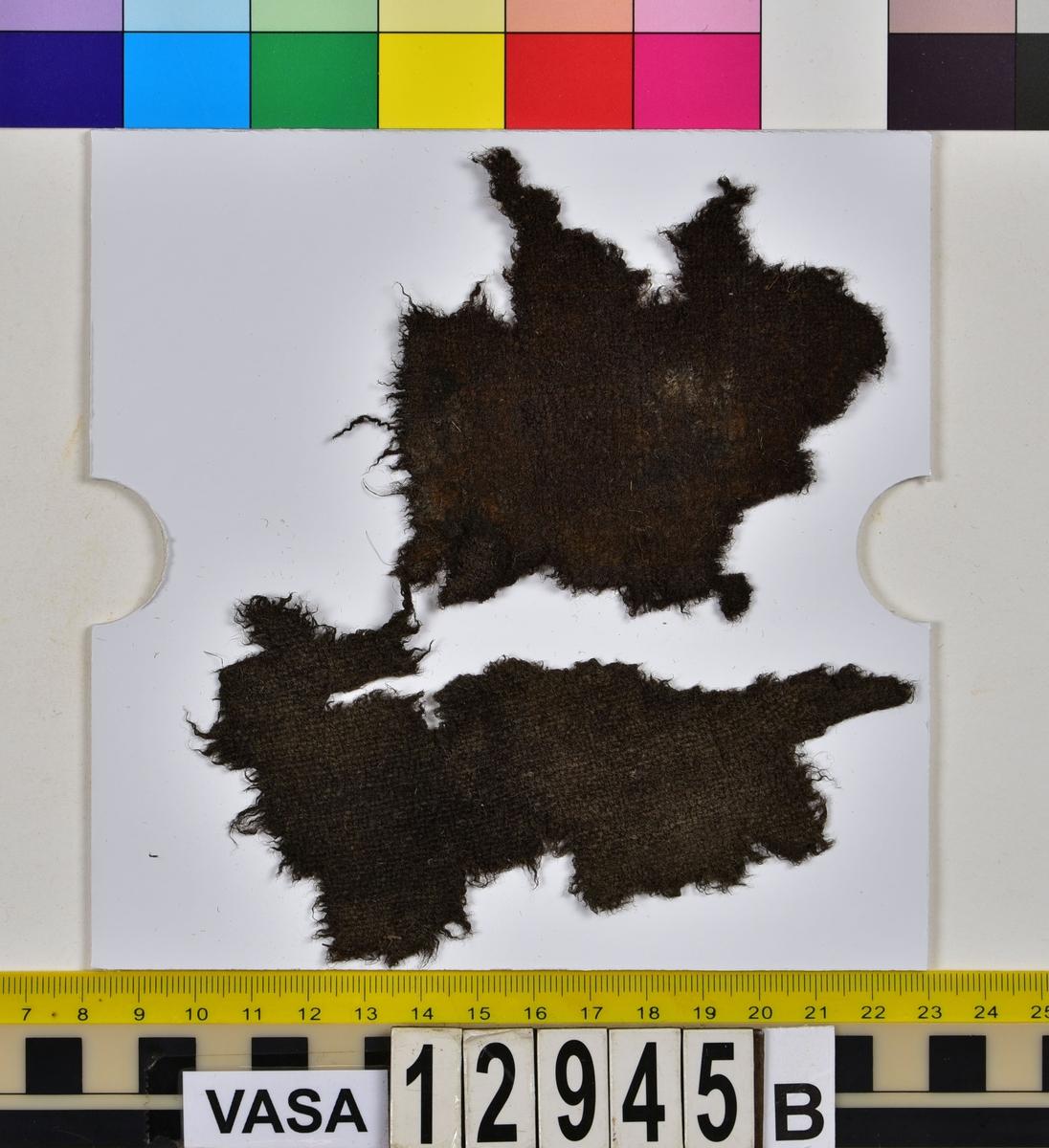 Textilfragment. 15 textilfragment uppdelade på fyndnummer 12945a-g. Fnr 12945a består av fyra fragment av ull vävda i tuskaft. Två av fragmenten har rester av söm eller fåll samt har varit valkade. Fnr 12945b består av två fragment av ull vävda i tuskaft.  Fnr 12945c består av ett fragment av ull vävt i tuskaft. Fragmentet kan ha varit valkat på ena sidan. Fnr 12945d består av ett fragment av ull vävt i tuskaft. Fragmentet har en söm med rester av stygn kvar i ena kanten. Fnr 12945e består av tre fragment av ull vävda i tuskaft. Fragmentet har en tydlig originalkant bevarad. Fnr 12945f består av ett filtat fragment. Kan möjligen ha varit en del av ett hattbrätte. Fnr 12945g består av tre filtade fragment, troligen av ull.