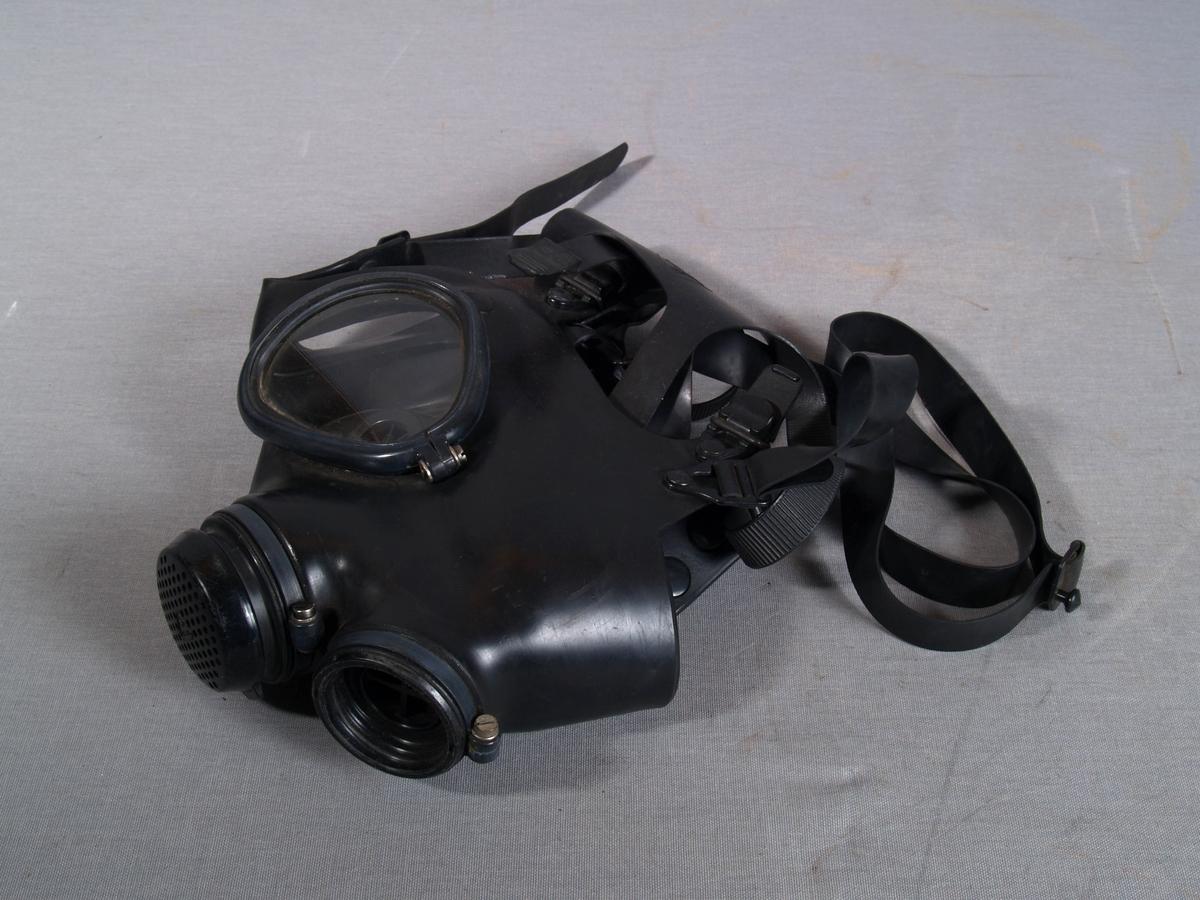 Gassmaske i gummi, med delt plastvindu i rammer av plast. Ventil i metall. Gjenget tilslutning for friskluftslange. Regulerbare gummi  remmer for feste rundt hodet