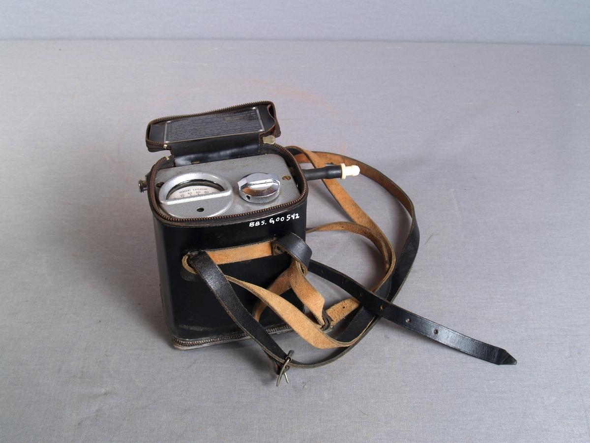 Gassdetektor i lærveske. Detektoren er i metall med glassvindu for visning av gassnivå i luften. Sensor som stikker ut på siden av apparatet. Bærestropp festet på vesken,lokket lukkes med glidelås. Instrumentet har rektangulær form.