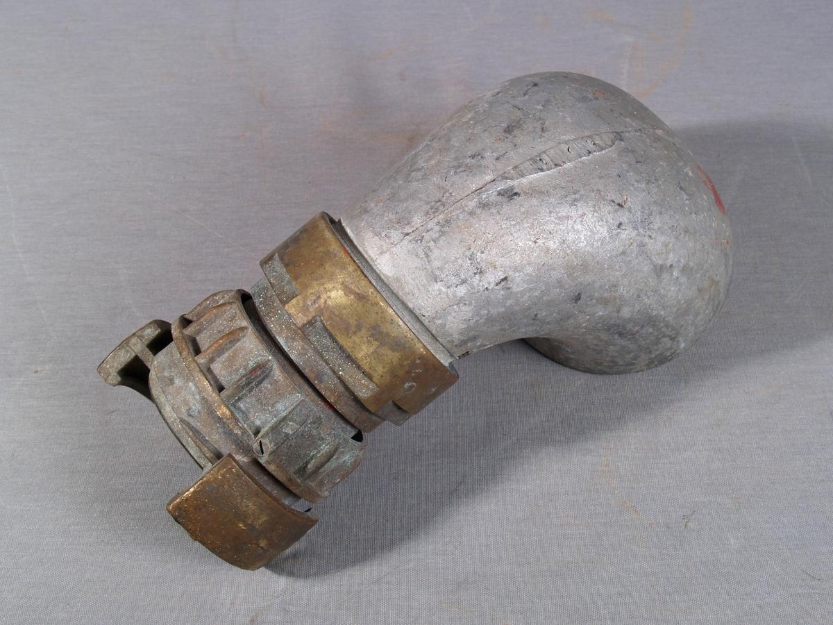 Fylletut i metall formet som et horn/trakt med oval åpning i ene enden og stuss for kobling i andre enden. Helstøpt i metall.