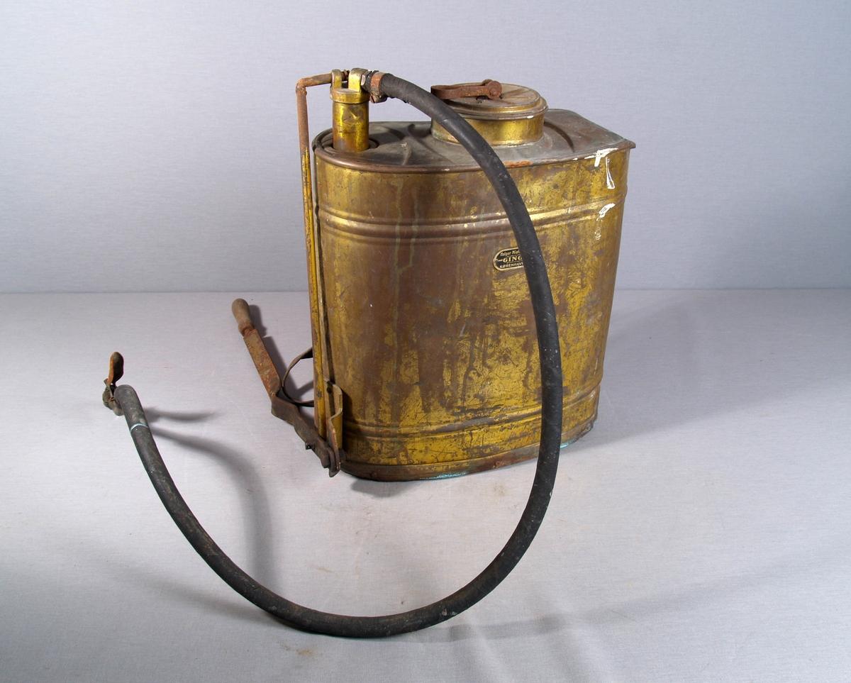 Brannsprøyte til å bære på ryggen. Oval form, påfylling for vann og utløp for slangen på toppen, på venstre side nede et håndtak for å pumpe vannet opp i slangen. Slangen har hendel for åpning og lukking av slangetuten. Bæreselene er festet bak, nede på sidene og oppe på midten