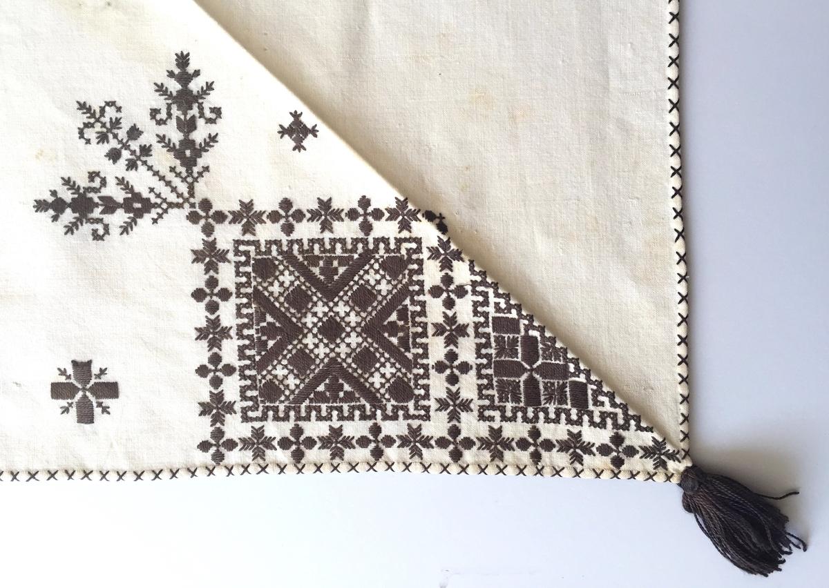 Plattsömsmotiv i kvadraterna på ryggsnibben, kvistar och blomsterliknande motiv, bård saknas. 2 st ornament i plattsöm
