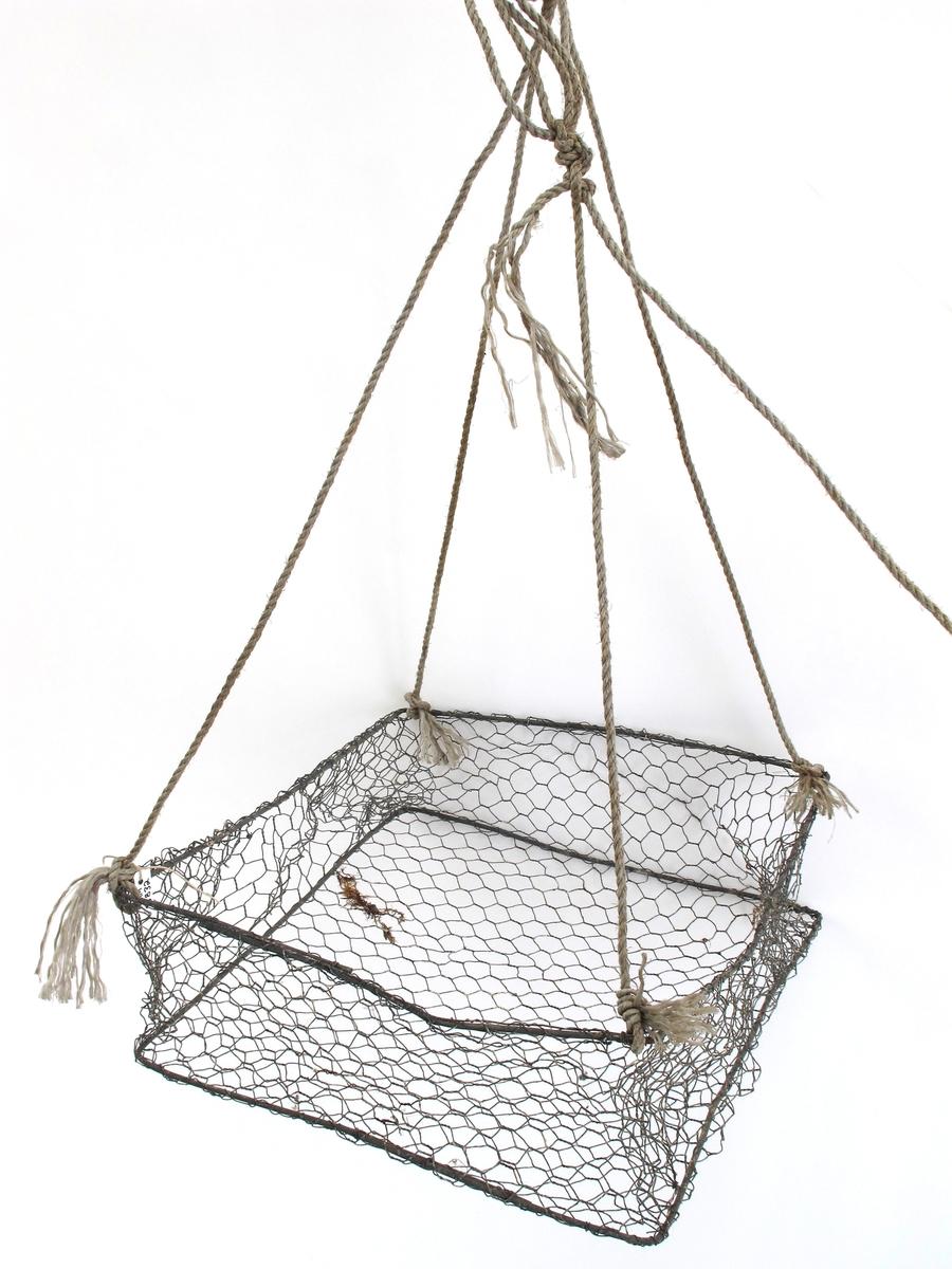 Kurv, firkantet, laget av netting og ståltråd. Med tau, som er festet i alle 4 hjørner. Tauet er til løfting.
