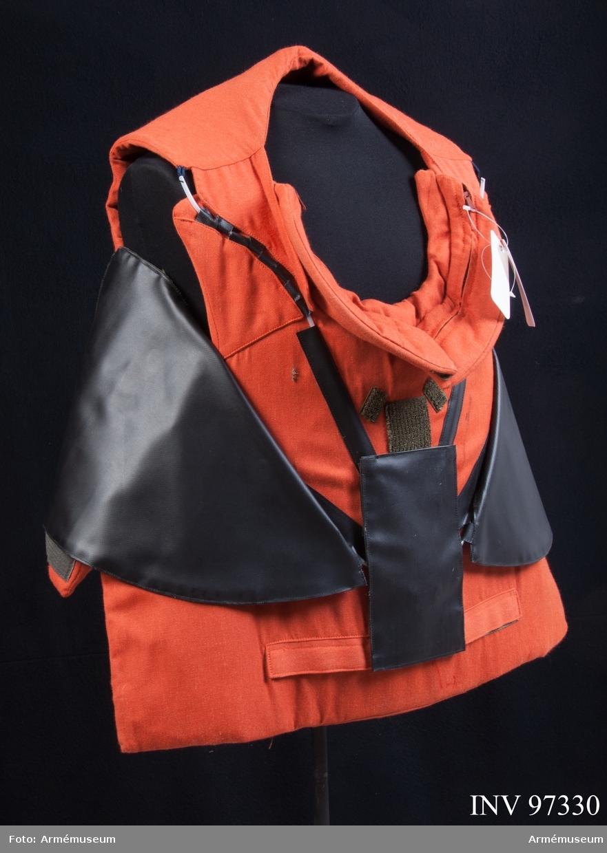 """Kroppsskyddsväst i orange textil med insydda plattor. Vissa delar av västen är i svart plast. I västen finns en etikett med följande text: """"ccp 9349. Stature C. Induyco Madrid""""."""