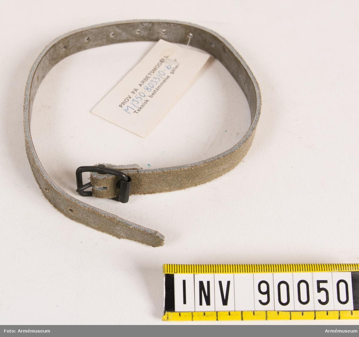 """Rem av läder med 15 spännhål och spänne av metall. Vidhängande lapp med text: """"Prov på arbetsmodell M 1350-803310-6 Teknisk bestämmelse gäller."""""""