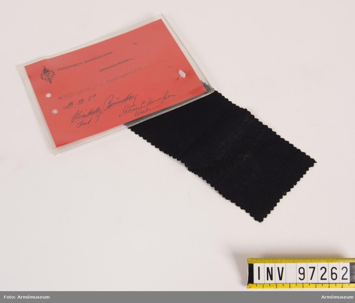 """Vidhängande modellapp med text: """"Försvarets materielverk. Originalmodell. M 1016-509150-0. Ripsdiagonal, blå. 1985-08-07. Elisabeth Rönnberg IntT, Göran Olmarker QInt."""""""