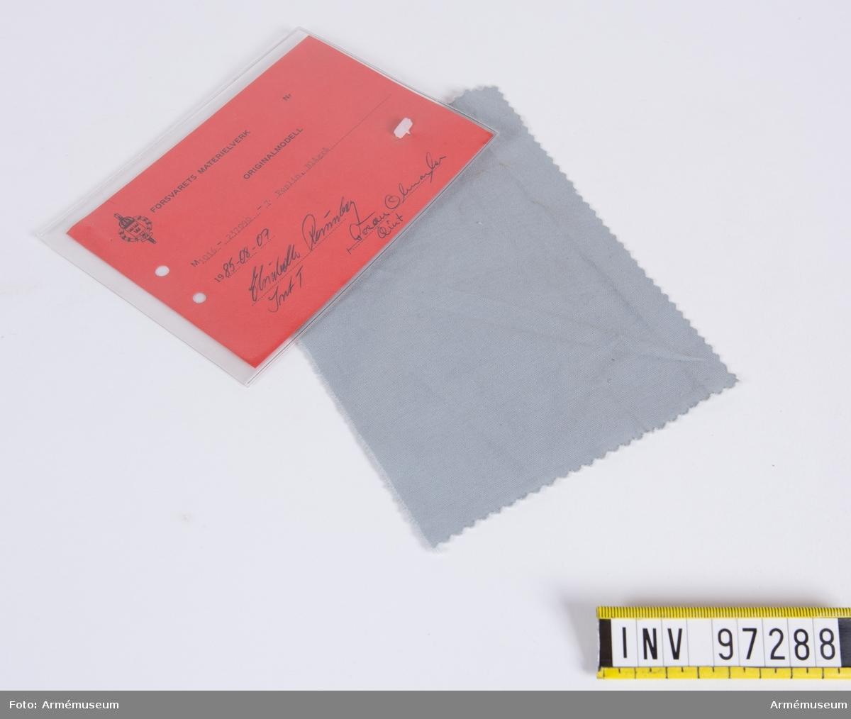 """Vidhängande modellapp med text: """"Försvarets materielverk. Originalmodell. M 1016-237090-7 Poplin, Blågrå. 1985-08-07. Elisabeth Rönnberg IntT, Göran Olmarker QInt."""""""